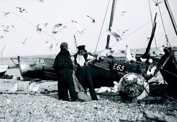 Three fishermen standing by their boats as seagulls hunt for scraps  c 1930s.