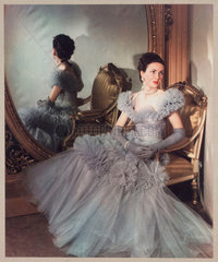 Woman modelling a ball gown in front of a mirror  c 1940s.