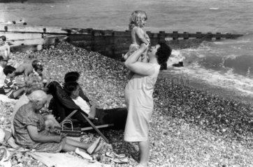 Woman holding child on shingle beach with other members of family  1969.