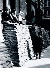 Men resting on top of piles of sandbags  WWII  London  4 September 1939.