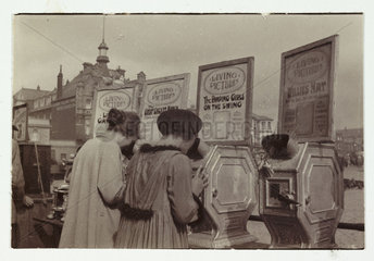 Women looking at 'What the Butler Saw' machines'  c 1910.