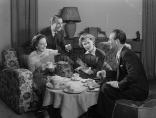Two couples having tea and cake  1949.