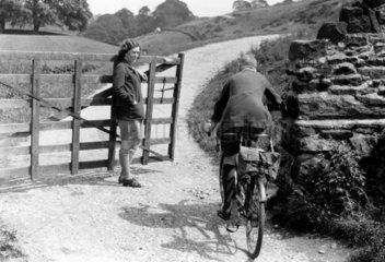Woman in a country lane holding a wooden ga
