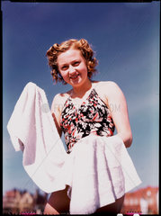 Woman in swimsuit with towel  c 1945.