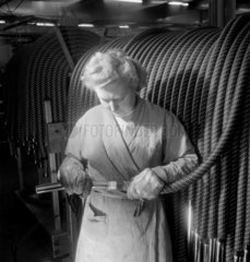 A female production worker fits pipes to hoover nozzels  Perivale  1949.