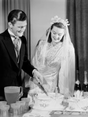 Bride and groom cutting their wedding cake  c 1949.