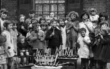 Children eating toffee apples  c 1930s.