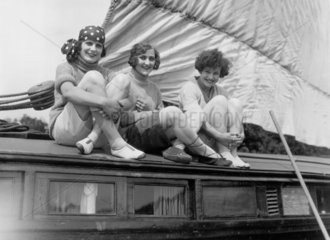 Three women sitting on a barge  smiling for