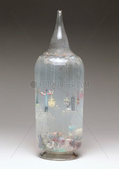 Large glass bottle containing glass amulets  French  c 1870-1920.