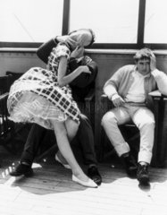 Man sitting beside a couple kissing on the