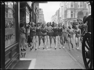 Women wearing swimsuits in a London street  1932.