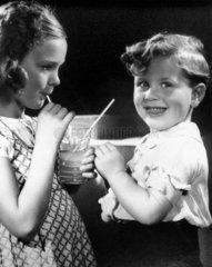 Children sharing a drink  1940s.