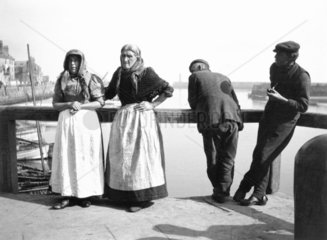 Four fisherfolk standing on a jetty in Whitby  North Yorkshire  c 1900s.