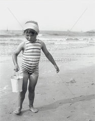 Small girl carrying a bucket on the beach  1910-1930.