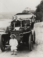 Two children with a car  c 1900s.