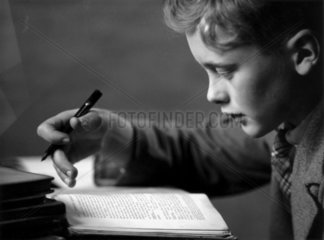 Schoolboy doing his homework  c 1930s.