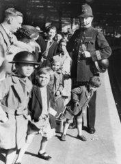 Evacuees with policeman on station platform  28 September 1940.
