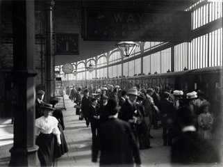 Railway travellers on a platform  c 1900s.