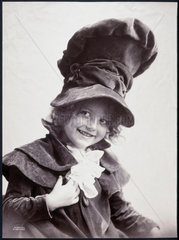 Smiling child wearing a huge velvet hat with matching velvet jacket  1900.
