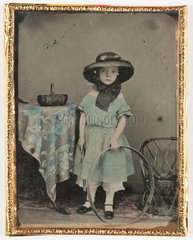 Portrait of a girl holding a hoop by a table  c 1840-1890.