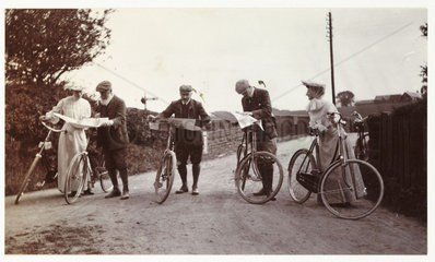Cyclists looking at maps  c 1900.