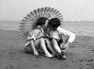 Girl and boy kissing under a parasol  c 1930s.
