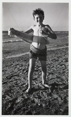 Young boy on a beach after a swim  c 1935.
