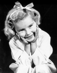 Little girl with a ribbon in her hair  c 1940s.