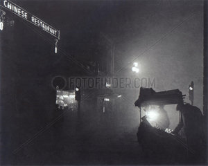 'A foggy Piccadilly partially lit by the light from a fruit seller's stall'  1952.