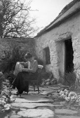 Woman reading a newspaper in a cottage gard