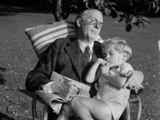 A boy and his grandfather in a chair in the garden  c 1930s.