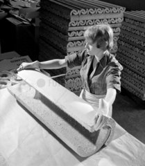 A female worker finishes asbestos pipe sections at Thomas Ward Asbestos.