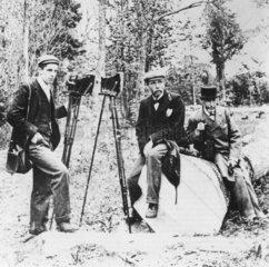 Three men with field cameras on location  c 1880.
