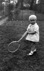 Small child holding a large tennis racquet  c 1920s.