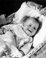 A happy baby lying in a cot  1940s.