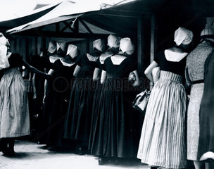 Women in traditional Dutch dress at a market  Holland  c 1920s.