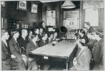 Men listening to a wireless concert  c 1920s.