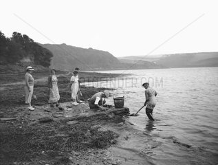Oyster fishers watched by tourists  Percuil  Cornwall  1937.