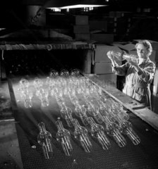 Female worker at a Lehr kiln inspects glass for mercury vapour lamps  1960.
