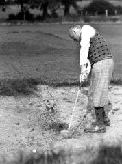 Golfer wearing plus fours striking his ball