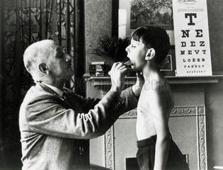 A doctor checks a young boy's tonsils  December 1935.