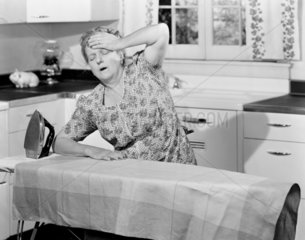 Middle-aged woman distressed by ironing  c 1940s.
