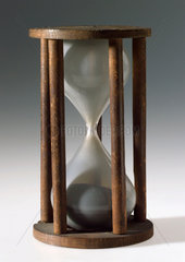 Single sand glass in five pillared wooden mount  18th century.