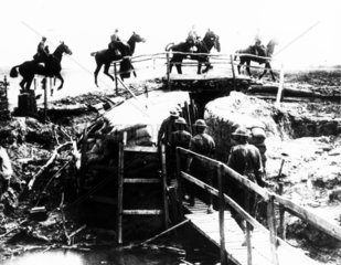 Australian Mounted Cavalry crossing a wooden bridge over a trench.
