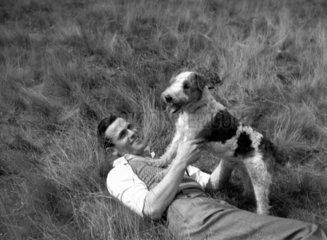 Man playing with a dog  c 1930s.