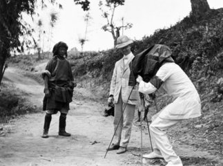 Two colonials taking a photograph of a 'native'  c 1900s.