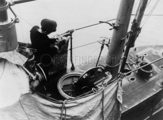 Officer of a submarine fixing a message to the leg of a carrier-pigeon  1914-1918.
