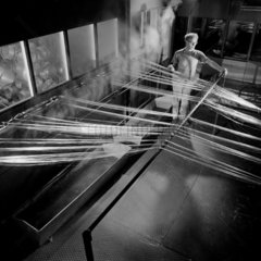 Fibre glass production: a worker at steam bath section outside creel room.