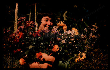 Woman holding flowers  c 1940.