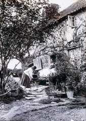 Woman at cottage door  late 19th century.